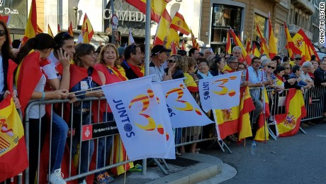 "Anti-independence protesters in Barcelona on Sunday holding Spanish flags, as well as others that say ""together."""