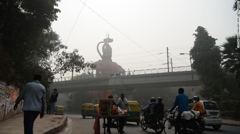 Indian commuters drive past the city's famous Hanuman Temple amid heavy smog.