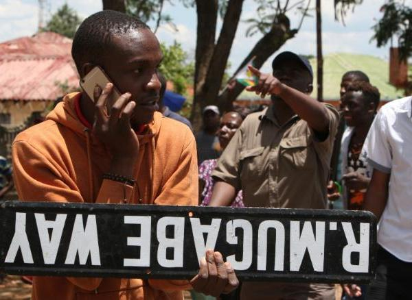 """A man holds a street sign as hundreds gather in Bulawayo, Zimbabwe, on Saturday, November 18, <a href=""""http://edition.cnn.com/2017/11/18/africa/zimbabwe-anti-mugabe-rally/index.html""""  demand the resignation of President Robert Mugabe</a>. The army put Mugabe -- the 93-year-old leader who has ruled the country for nearly four decades -- under house arrest just days earlier and detained some of his key political allies."""