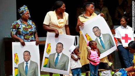 Supporters hold portraits of Emmerson Mnangagwa at his inauguration.