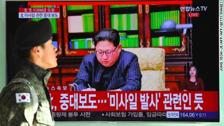 A South Korean soldier walks past a television showing North Korean leader Kim Jong Un approving the first test of the Hwasong-15.