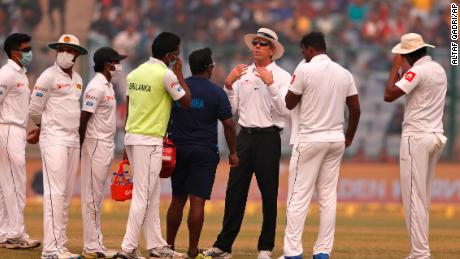 Officiating umpire Nigel Llong, third from right, addresses Sri Lanka's players wearing masks, during a brief break on Sunday's match.