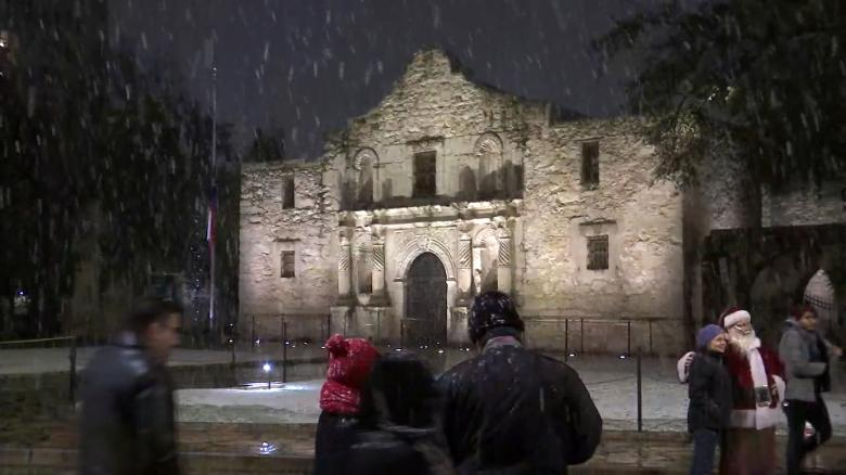 People watch the snowfall outside the Alamo in San Antonio, Texas.