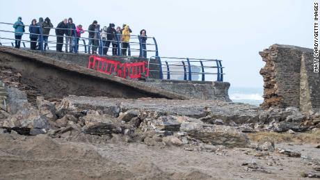 People stop to look at damage to the harbor wall caused by Storm Eleanor in Portreath, Cornwall, in the UK.