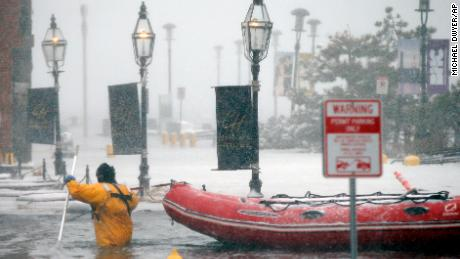 A Boston firefighter wades through floodwaters from Boston Harbor on Thursday, January 4, on Long Wharf in Boston.