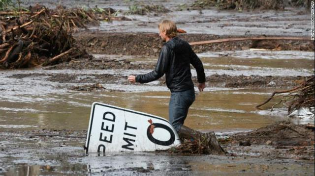 Phillip Harnsberger crosses through mud from a flooded creek in Montecito on Tuesday, January  9. Heavy rains unleashed destructive rivers of mud and debris in Southern California. At least 15 people have died.