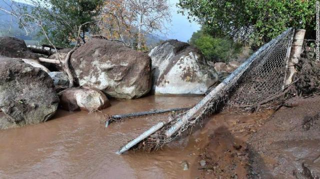 Boulders carried downhill in the flooding rest against a broken fence Tuesday in Carpinteria, California.