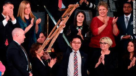 North Korean defector Ji Seong-ho raises his crutches as US President Donald Trump delivers the State of the Union address at the US Capitol in Washington, DC, on January 30, 2018. / AFP PHOTO / SAUL LOEB        (Photo credit should read SAUL LOEB/AFP/Getty Images)