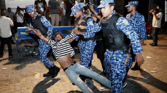 Maldivian police officers detain an opposition protestor demanding the release of political prisoners in Male on February 2.