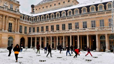 Children play in the snow in the Palais Royal garden on Wednesday.