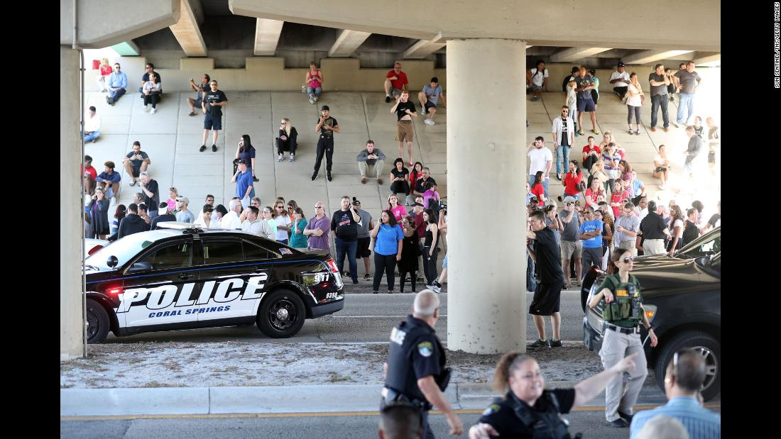Family members wait for word from students beneath an underpass just south of the campus of Marjory Stoneman Douglas High School.