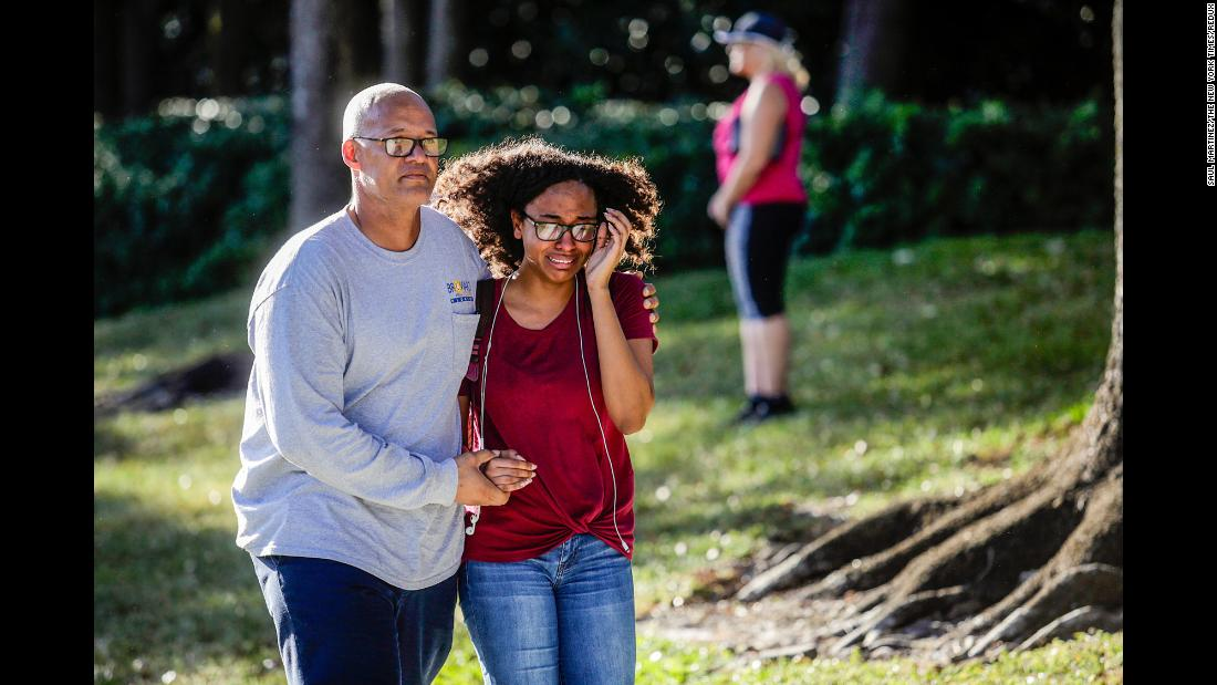 A father and daughter embrace after a mass shooting at the Marjory Stoneman Douglas High School.