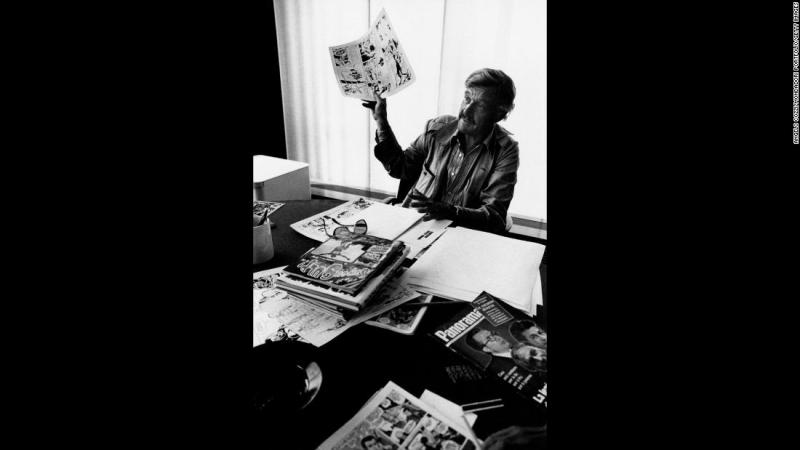 Lee, born Stanley Martin Lieber, holds up comic book art during the 1970s. In 1941, he became the editor at Timely Comics, which evolved into Marvel Comics.