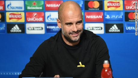 Manchester City's Spanish manager Pep Guardiola wears a yellow ribbon on his jumper, in support of those currently in detention in Catalonia, during a press conference.