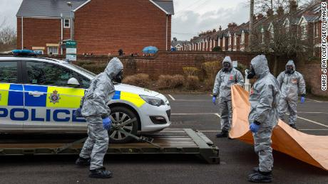 Military personnel wearing protective suits remove a police car from a parking lot as they investigate the poisoning.
