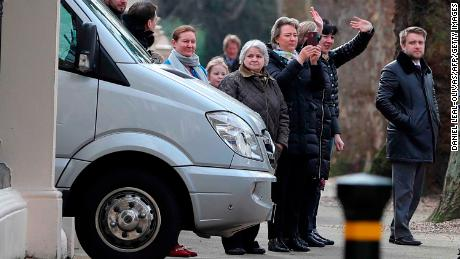 People wave to others aboard diplomatic vehicles leaving the Russian Embassy.