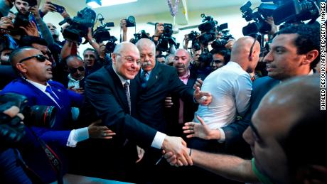 Egyptian presidential candidate Mousa Mostafa Mousa shakes hands with supporters ahead of casting his vote Monday.