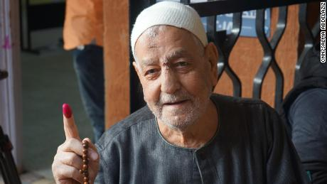 An elderly voter shows his ink-stained finger after voting in Cairo's Gamalya, the neighborhood where Sisi was born.