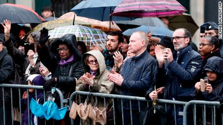 People applaud while Beltrame's coffin passes in central Paris.