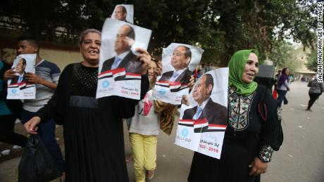 A woman holds a poster of Egyptian President Abdel Fattah al-Sisi on the last day of voting in Cairo.