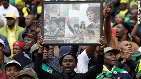 A man holds up a frame showing newspaper clippings of Madikizela-Mandela.