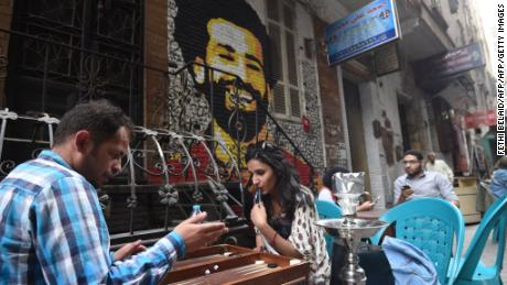 Egyptians gather at a cafe near a graffiti of Egyptian footballer Mohamed Salah in Cairo.