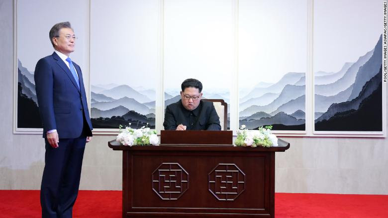 North Korean leader Kim Jong Un signs the guest book as South Korean President Moon Jae-in looks on.