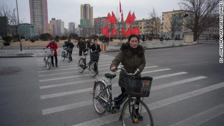Cyclists cross a road in Kaesong, North Korea. A joint industrial complex once run in the city by the South and North Korean has been considered a possible model for future ties.