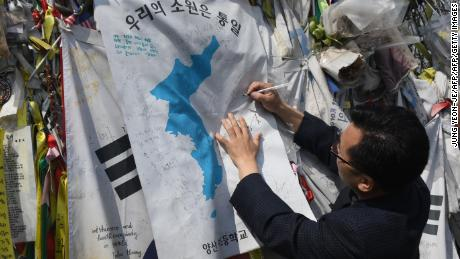 """A man writes an inscription calling for peace and reunification on a """"Unification flag"""" hanging at a military fence at Imjingak peace park in Paju near the demilitarized zone dividing the two Koreas on April 26, 2018."""