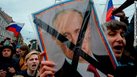 Protesters hold placards of Russian President Vladimir Putin during Saturday's rally.