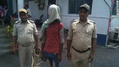 A suspect (C) being held by Indian police in the case of a 17-year-old girl who was raped and set on fire.