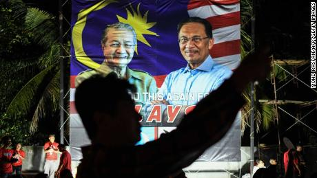 A supporter takes pictures in front of a banner showing Mahathir Mohamad, left, and jailed  opposition leader Anwar Ibrahim, right, during an April 15 election rally on Malaysia's island of Langkawi.