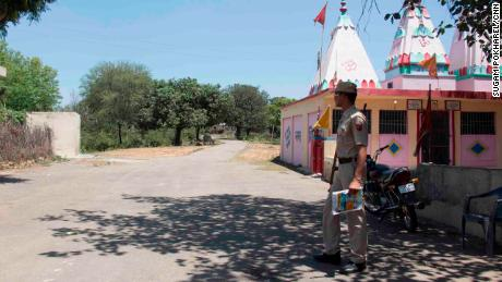 A police officer guards the main entrance to Rasana village. Local police have increased their presence in the village following the rape and murder of the Muslim girl.