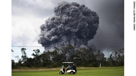 A man drives a golf cart at a golf course as an ash plume rises in the distance from the Kilauea volcano on Hawaii's Big Island
