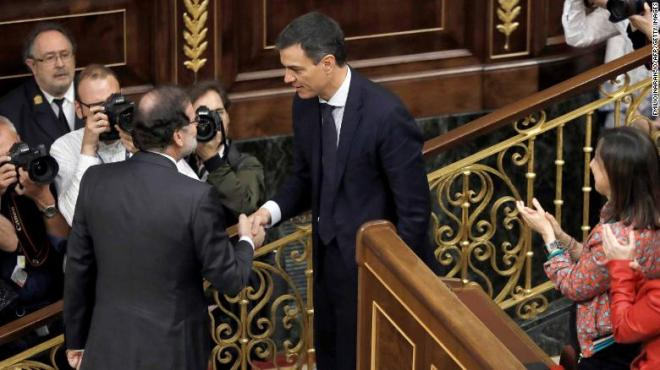 Outgoing Prime Minister Mariano Rajoy, left, shakes hands with Spain's new Prime Minister Pedro Sanchez after the vote.