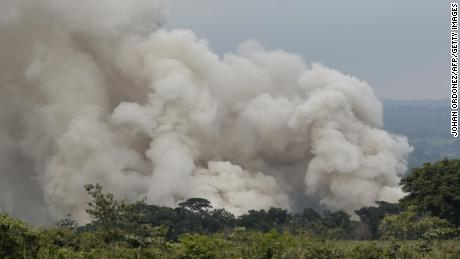 A smoke column forced rescuers to evacuate the village of San Miguel Los Lotes on Tuesday.