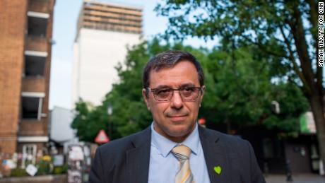 Survivor Miguel Alves wearing a commorative green heart in front of Grenfell Tower.