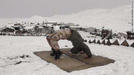 A member of the Indo-Tibetan Border Police practice wheel pose at a military base in the Himalayan mountains.