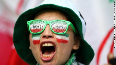 A female Iranian fan cheers on her team against Morocco.