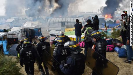"""French anti-riot police officers arrive in October 2016 to clear the Calais """"Jungle""""."""