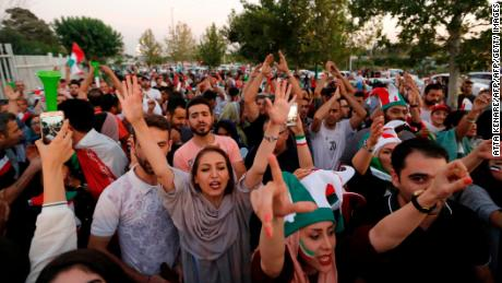 Iranian football supporters arrive at the Azadi Stadium to watch the match against Spain on a big screen.
