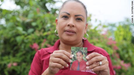 "Daniel Vick's mother, Margarita Rodriguez, holds a photo of her son, whose death was labeled ""leptospirosis"" in a database obtained by CNN and CPI."