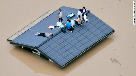 People wait to be rescued on the roof of a house in Kurashiki, Okayama prefecture.