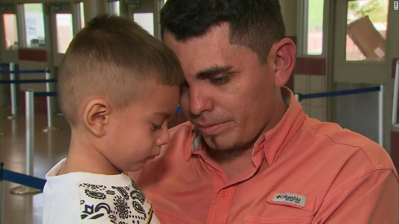 Josue Rodriguez holds his 3-year-old son after being separated for 40 days.