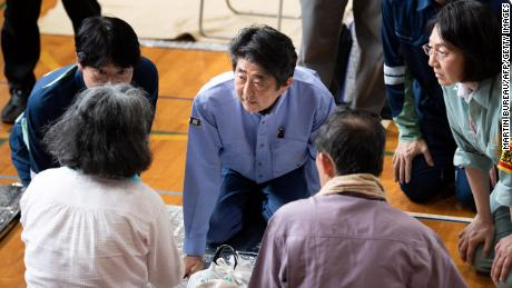 Japan's Prime Minister Shinzo Abe visits a shelter for people affected by the recent flooding in Mabi, Okayama prefecture on July 11, 2018.