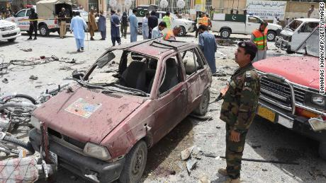 Pakistani volunteers and security officers visit the site of the bombing Wednesday in Quetta.