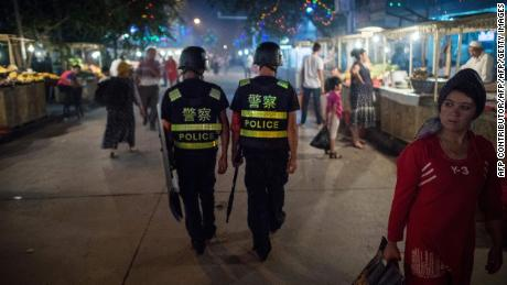 This picture taken on June 25, 2017 shows police patrolling in a night food market near the Id Kah Mosque in Kashgar in China's Xinjiang Uighur Autonomous Region, a day before the Eid al-Fitr holiday.