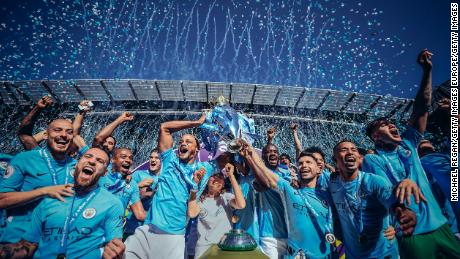Vincent Kompany and Sergio Aguero of Manchester City lift the Premier League trophy following their win over Huddersfield Town at the Etihad Stadium.