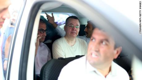 Andrew Brunson, au centre, est aperçu à l'intérieur d'une voiture escortée par des policiers turcs en civil alors qu'il arrive chez lui à Izmir le 25 juillet.