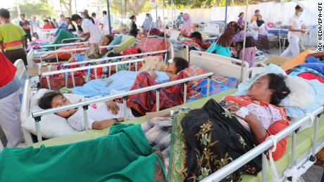 Patients in their beds are moved to an emergency tent outside of the Tanjung hospital, Lombok.